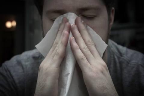 אדם מקנח את האף
