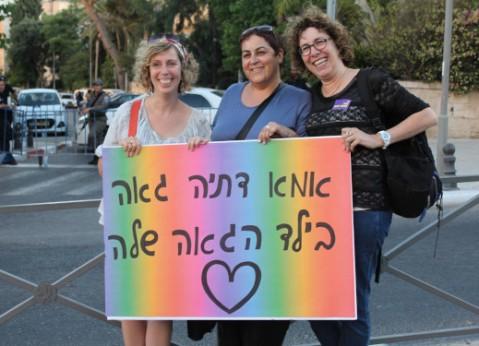 """שלשוש אמהות מחזיקות שלט שעליו כתוב: """"אמא דתיה גאה בילד הגאה שלה"""""""
