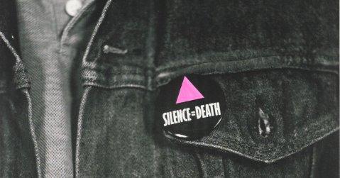 """ז'קט ג'ינס עם סיכה שעליה כתוב """"שתיקה=מוות"""" ומצוייר משולש ורוד"""